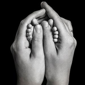 kleine zehen zwischen mamas händen in schwarz weiß. schwarz weiß fotos sehen sehr schön aus bei babyhänden und -füßen